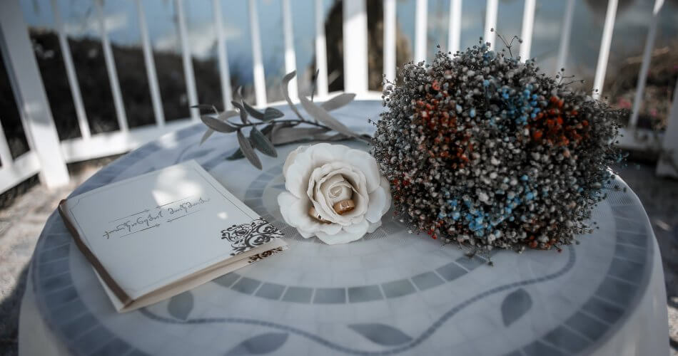 rose with engagement rings and vows on table